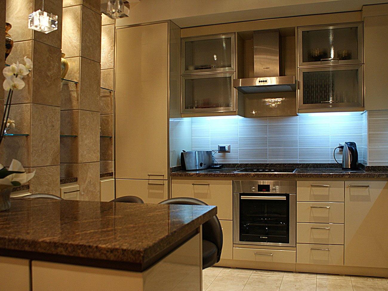 фото открытой небольшой кухни с барной стойкой, мебелью и необходимой техникой