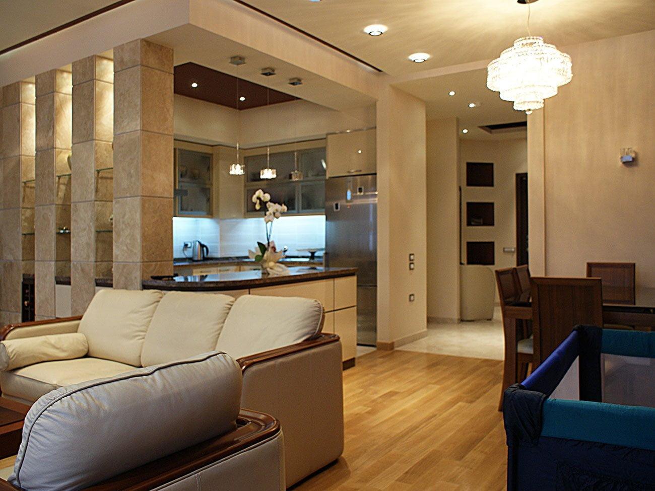 фото гостиной с ТВ зоной, зонированой большими диванами с видом на кухню и холл