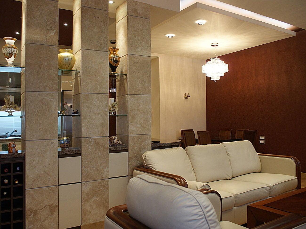 фото лёгких колонн, отделяющих кухню от гостиной и ТВ зоны с кожаным диваном