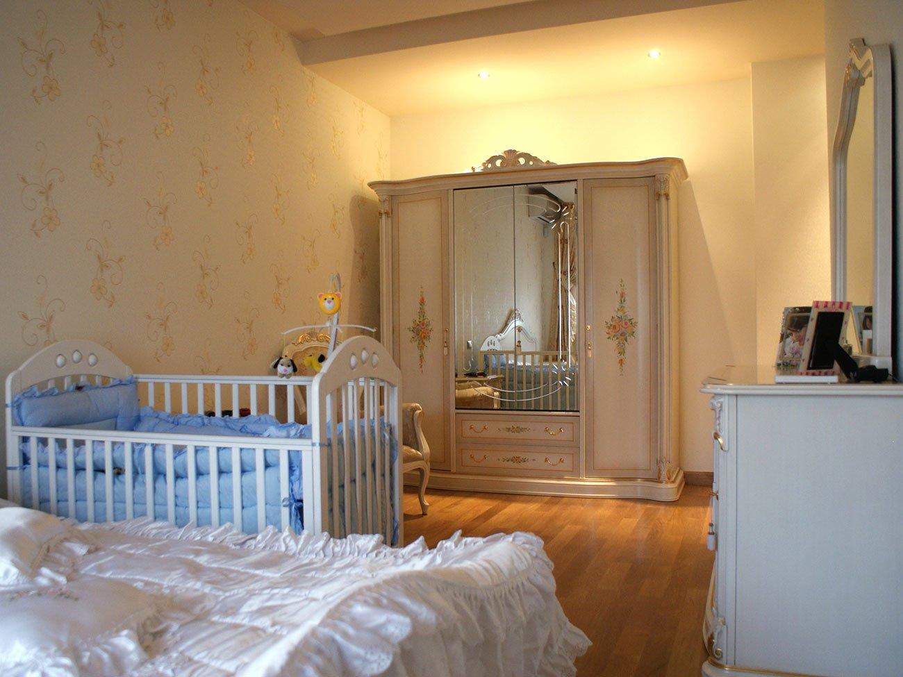 фото спальни, где тёплое освещение и хрустальная люстра смягчает прямые формы