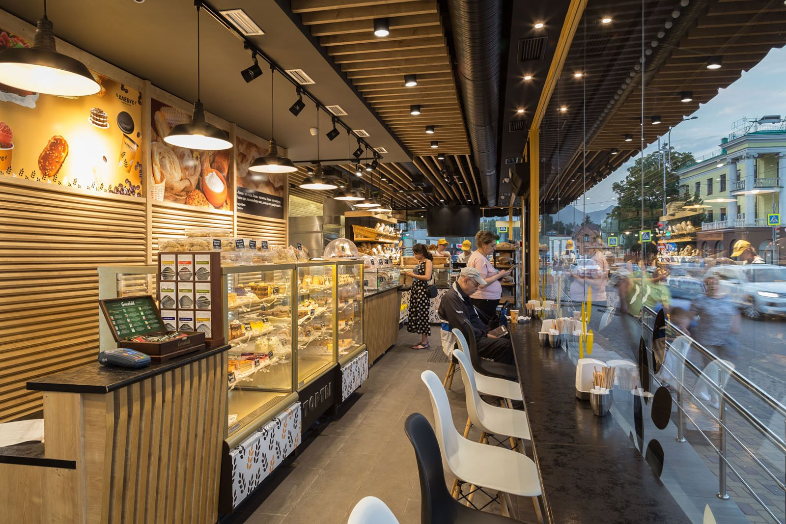 fotografiya inter'yera kafe v pekarne s vypechkoy i posetitelyam