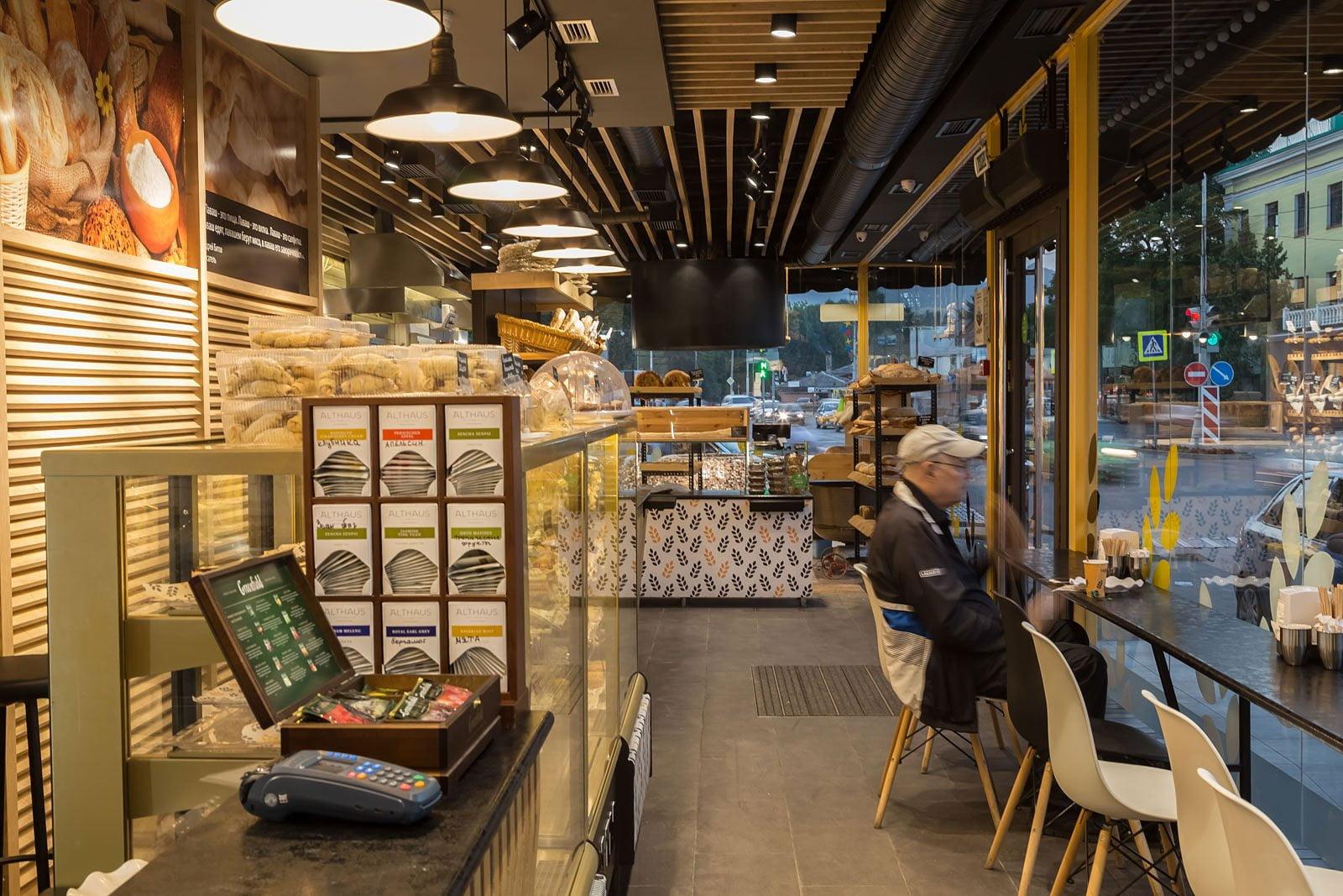 foto sprava vnutrennego inter'yera kafe v pekarne s posetitelem