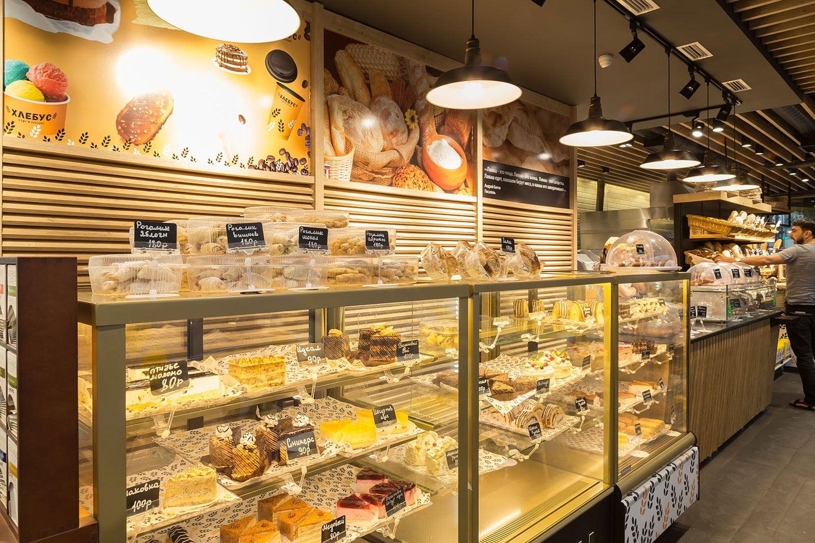 foto sprava vnutrennego inter'yera kafe v pekarne s prilavkami i vypechkoy