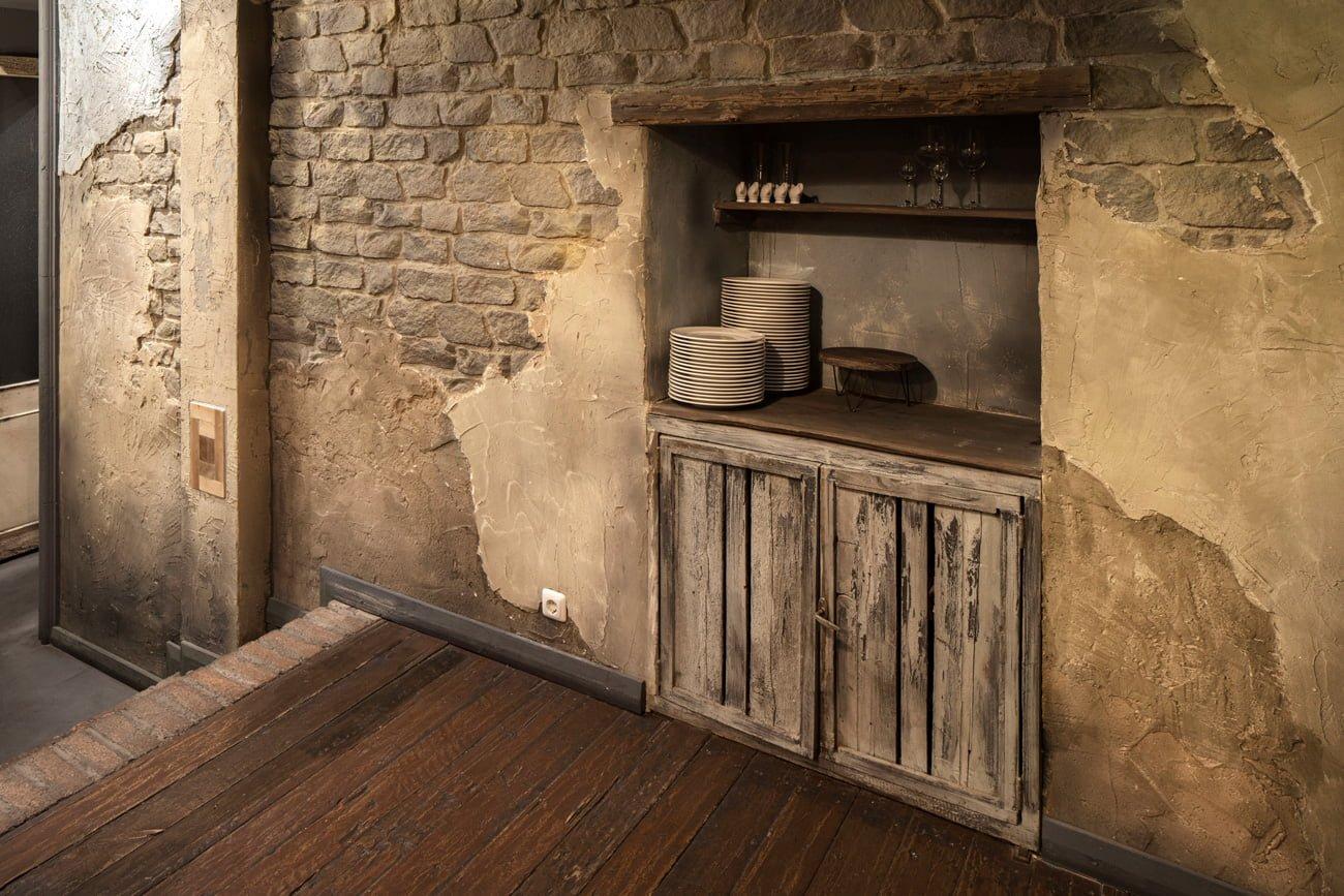 фото отделки интерьера ресторана с старинными дверцами погреба и глиняной посудой