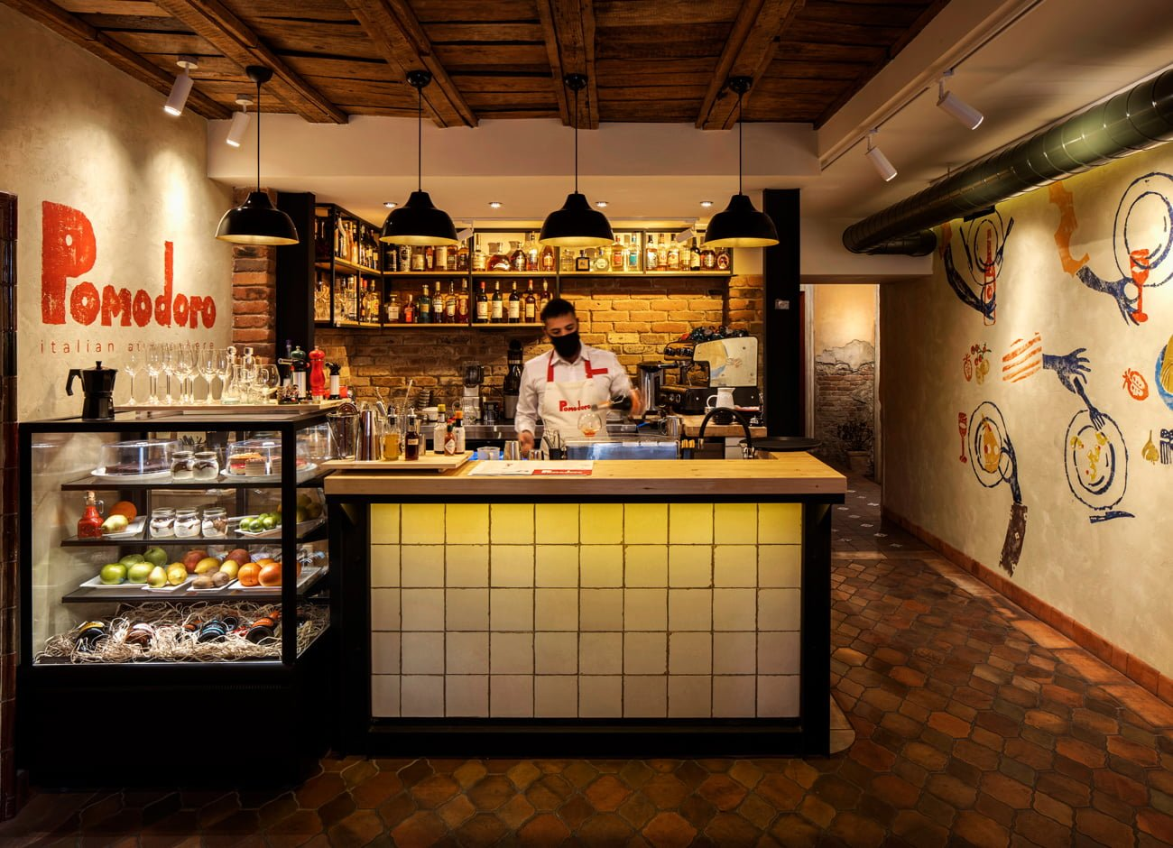 photo of a bar with a bar counter and a barista at the entrance to the POMODORO restaurant