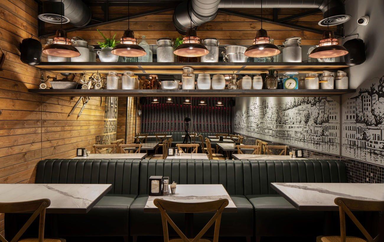 фото дизайнерского решения малого зала ресторана Grillian с мягкими диванами и столами
