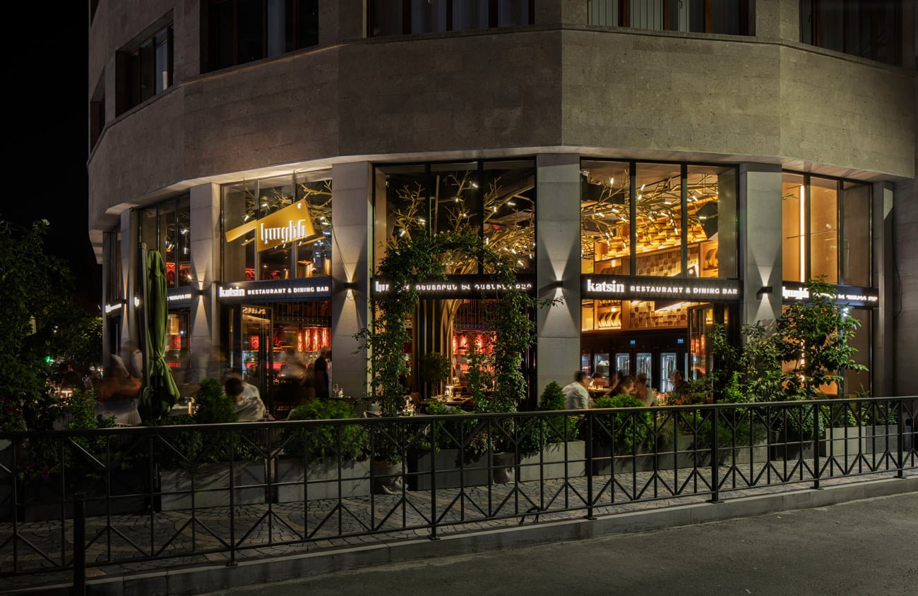 photo from the street of the Katsin restaurant with panoramic windows and a veranda with plants